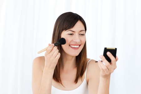 Lovely woman putting on make up  photo