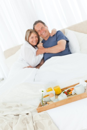 Lovely couple  having breakfast in their bed at home Stock Photo - 10197072