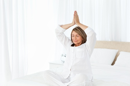 Senior practicing yoga on her bed at home photo