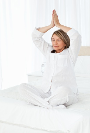 Senior practicing yoga on her bed at home Stock Photo - 10195360