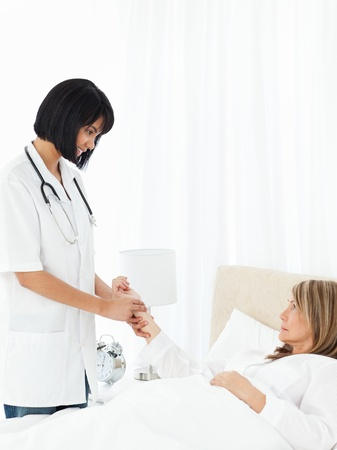 Nurse taking the pulse of  her patient photo