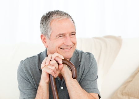 Mature man thoughtful with his walking stick on his bed at home photo