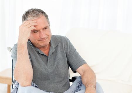 amputation: Senior in his wheelchair having a headache at home Stock Photo