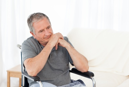 Senior in his wheelchair having a headache at home photo