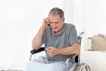 Senior in his wheelchair phoning at home photo