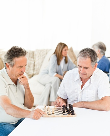 Seniors playing chess on the table photo