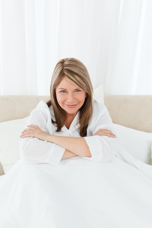 Portrait of a pretty woman on her bed at home photo