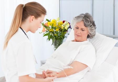 enfermera con paciente: Enfermera poniendo un goteo en el brazo de su paciente