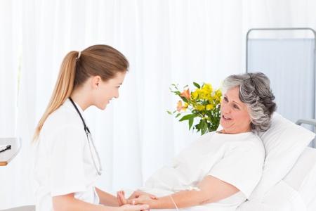 enfermera con paciente: Enfermera poniendo una gota en el brazo de su paciente