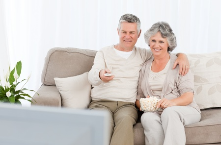 man couch: Mature couple watching tv in their living room at home