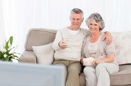 pareja viendo tv: Pareja joven viendo la televisi�n en su sala de estar como en casa