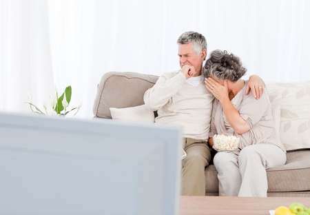 Mature couple watching tv in their living room at home photo