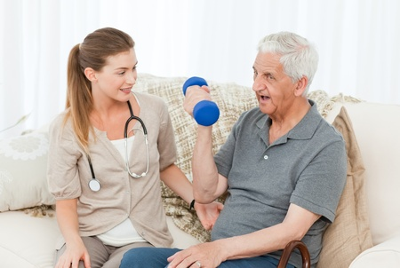 Lovely nurse helping her patient to do exercises at home Stock Photo - 10196825