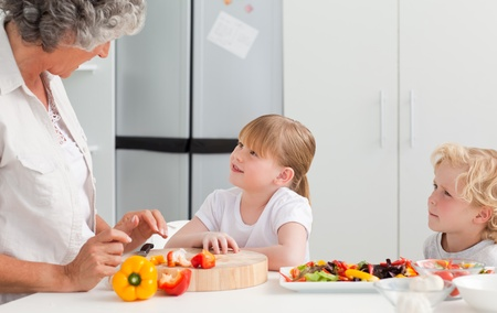 Little girl looking at her grandmother who is cooking at home  photo