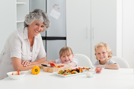 Children cooking with their grandmother at home photo