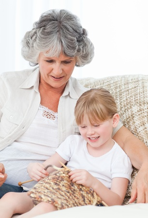 Grandmother helping her little girl to knit photo