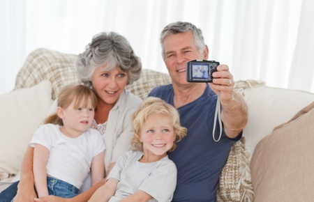 Family looking at their camera at home photo