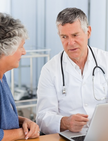 A senior doctor with his patient looking at the laptop in his office photo