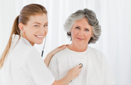 Retired patient with her nurse looking at the camera photo
