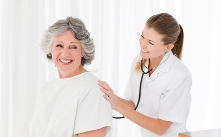 Pretty nurse taking the heartbeat of her patient Stock Photo - 10195331