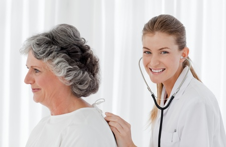 Pretty nurse taking the heartbeat of her patient Stock Photo - 10196958