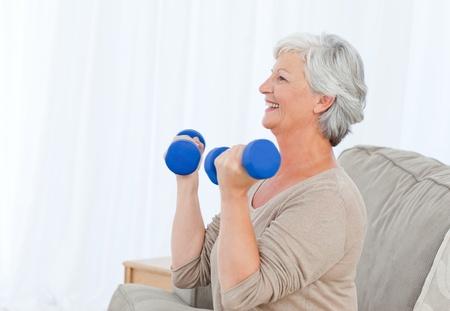 Senior doing her exercises on her sofa photo