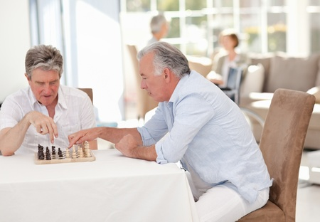 Seniors playing chess in the living room photo