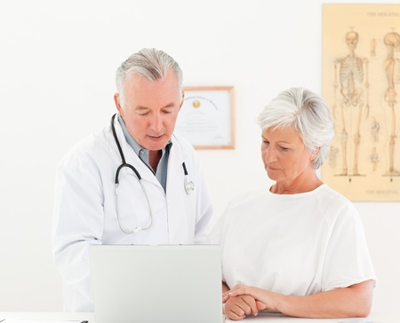 Doctor and his patient looking at the laptop photo