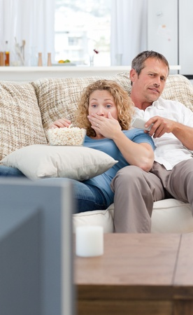 Lovers watching tv in the living room at home photo