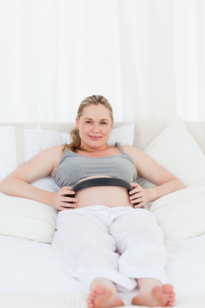 Pregnant woman putting her earphones on her belly at home Stock Photo - 10197091