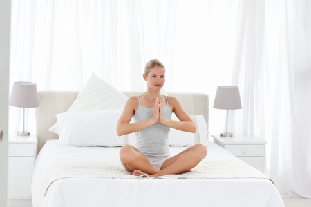 Beautiful woman practicing yoga on her bed at home Stock Photo - 10196915