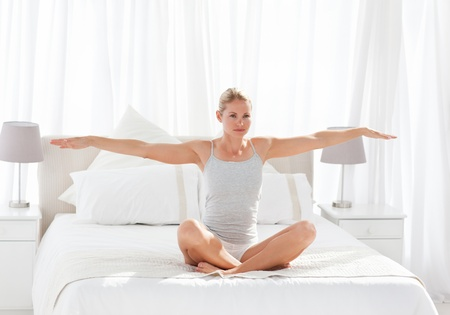 Beautiful woman practicing yoga on her bed at home Stock Photo - 10196922