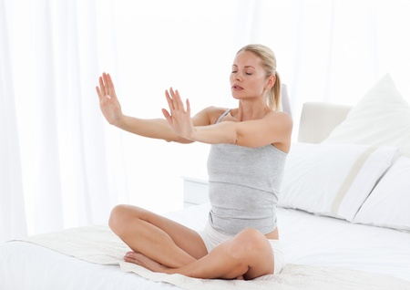 Beautiful woman practicing yoga on her bed at home Stock Photo - 10195478