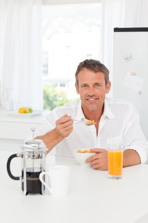Handsome man having his breakfast in the kitchen at home photo