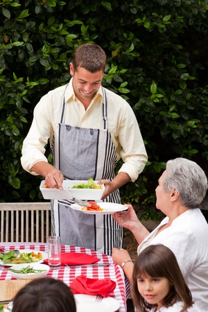 Man serving his mother at the table Stock Photo - 10185060