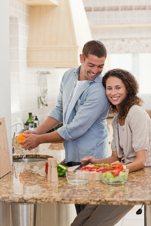 Woman eating while her husband is cooking at home photo