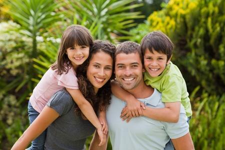familia en jardin: Madre y padre, dando a los ni�os un piggyback Foto de archivo