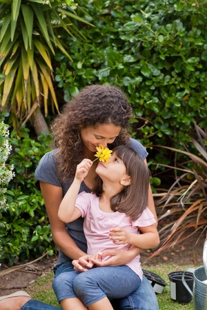 Mother smelling a flower with her daughter photo