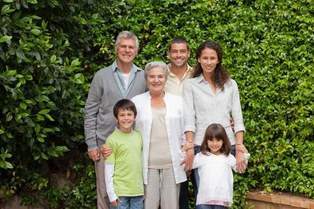 Portrait einer gl�cklichen Familie in die Kamera schaut in den Garten
