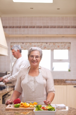 Retired woman looking at the camera in the kitchen Stock Photo - 10185142
