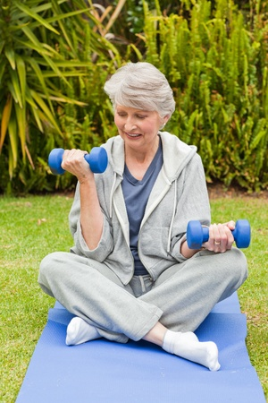 Retired woman doing her exercises in the garden photo