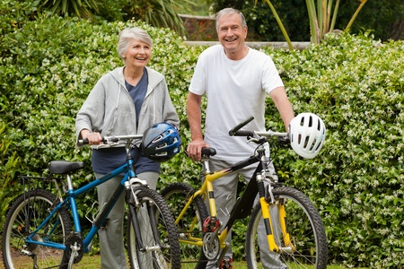 Mature couple walking with their bikes photo