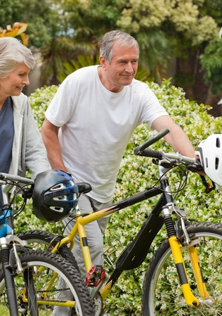 Mature couple walking with their bikes Stock Photo - 10197276