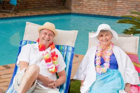 Senior couple lying down beside the  swimming pool photo
