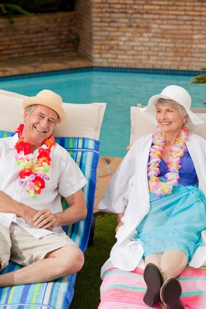 Senior couple lying down beside the  swimming pool photo