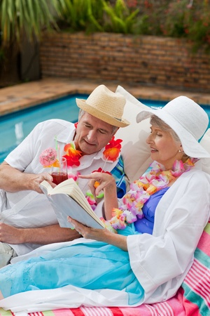 Mature woman reading a book while her husband is drinking a cocktail photo