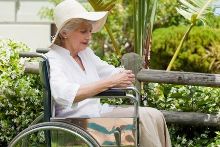 persona en silla de ruedas: Mujer madura en su silla de ruedas en el jard�n