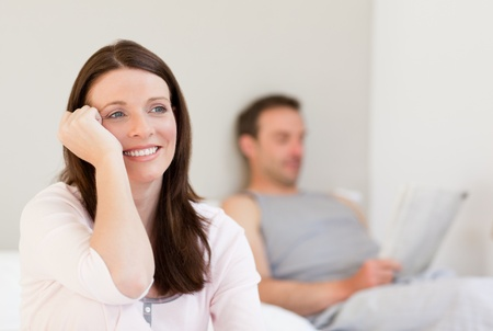 Lovely woman looking at the camera while her husband is reading a newspaper Stock Photo - 10183219