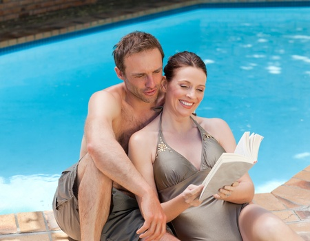 Couple reading a book beside the swimming pool photo
