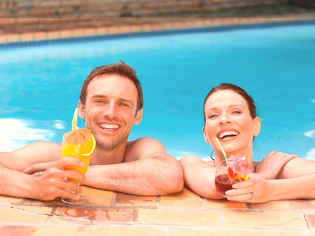 Beautiful couple drinking cocktails in the swimming pool photo